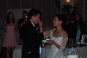 Carl and Jenny feed each other the first slice of cake. Photographer: James Wang